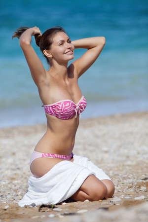 Aantrekkelijk meisje in badkleding met een witte handdoek aan de zee Jonge vrouw die zich op zee