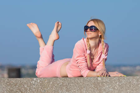 Attractive young woman in pink sportswear lying on front looking away  Girl in sunglasses resting on open air