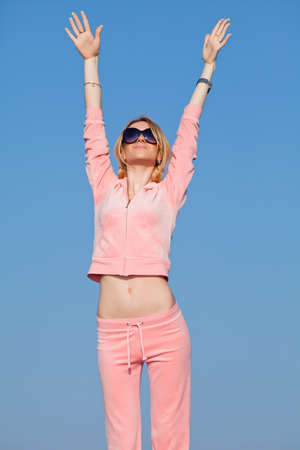 Attractive young woman in pink sportswear exercising against the sky   Girl in sunglasses outdoors photo