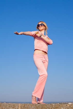 russian ethnicity caucasian: Attractive young woman in pink sportswear posing on background of sky  Girl in sunglasses on open air
