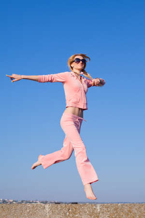 Attractive young woman in pink sportswear running on background of sky  Girl in sunglasses on open air photo