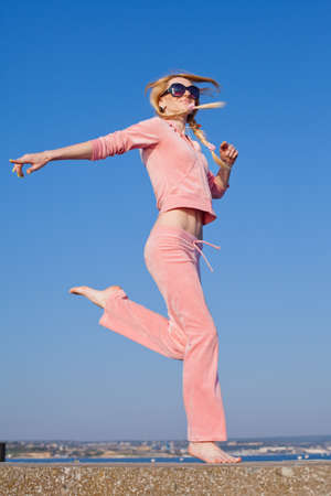 Attractive young woman in pink sportswear running on background of sky  Barefoot girl in sunglasses on open air photo