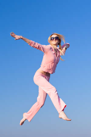 Attractive young woman in pink sportswear jumping on background of sky  Barefoot girl in sunglasses on open air photo