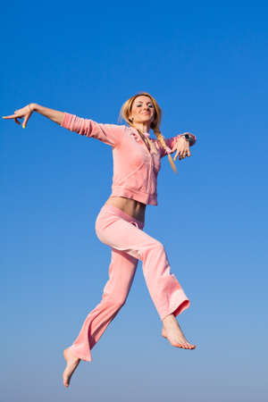 Attractive young woman in pink sportswear jumping on background of sky  Barefoot girl hopping on open air photo