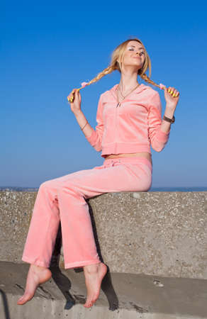 Attractive young woman in pink sportswear sitting on open air  Girl with eyes closed holding their pigtails