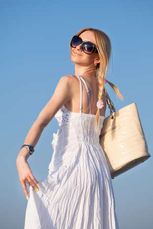 Attractive young woman in white sundress posing on background of sky  Girl with bag looking over shoulder  Stok Fotoğraf