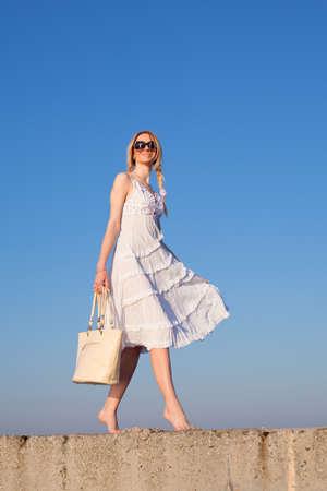 Aantrekkelijke jonge vrouw in het wit lopen Meisje met zak op de achtergrond van de hemel