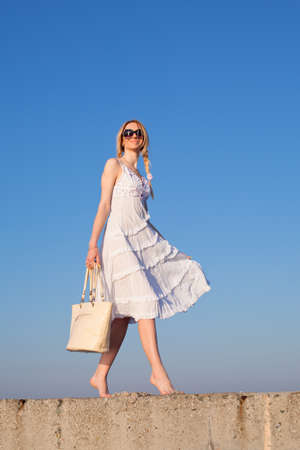 Attractive young woman in white walking  Girl with bag on background of sky