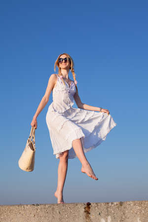 russian ethnicity caucasian: Attractive young woman in white walking  Girl with bag on background of sky