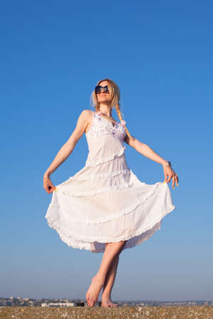 Attractive young woman in white posing on open air  Girl holding her skirt looks away photo