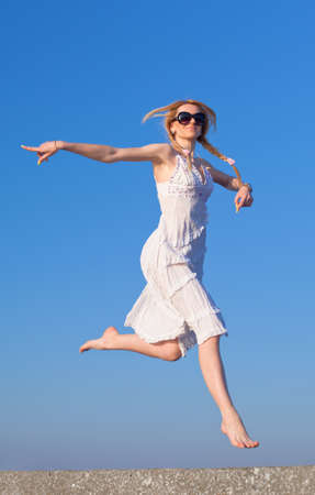 Attractive young woman in white sundress running on background of sky  Barefoot girl in sunglasses on open air photo