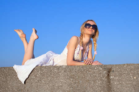 Attractive young woman in white sundress lying on open air  Girl in sunglasses on background of sky photo