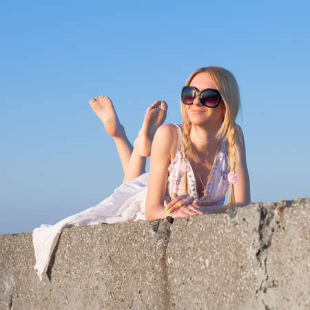 Aantrekkelijke jonge vrouw in witte sundress liggend op open lucht Meisje in zonnebril op achtergrond van de hemel