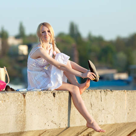 Attractive young woman in white sundress puts on shoes on open air  Girl with pigtails puts on shoes looking at camera smiling photo