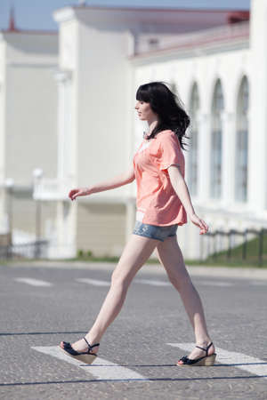 Brunette in shorts on open air. Attractive young woman in shorts walking along the crosswalk  photo