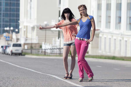 catching taxi: Girls on road. Two attractive young women catching taxi on the road Stock Photo