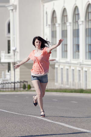 Brunette in shorts on open air. Attractive young woman in shorts running along the carriageway Stock Photo - 14330902