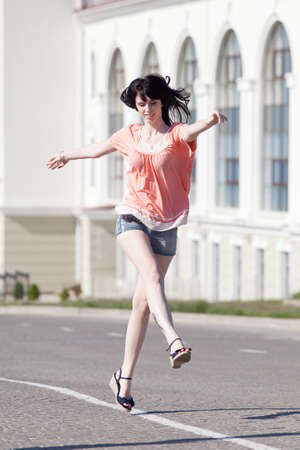 the carriageway: Brunette in shorts on open air. Attractive young woman in shorts running along the carriageway Stock Photo