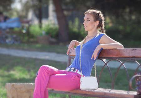 Meisje met pigtails op de open lucht. Jonge vrouw in roze broek zitten in de tuin op de bank Stockfoto