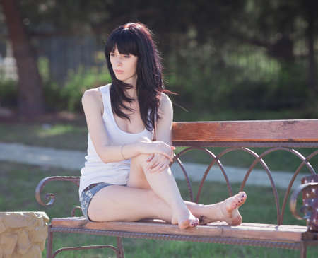 Brunette in shorts on open air. Attractive young woman in shorts sitting in garden on bench photo