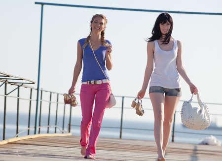 Meisjes op pier. Twee aantrekkelijke jonge vrouwen lopen langs pier Stockfoto