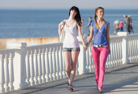Girls on quay. Two attractive young women walking along seafront