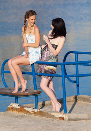 sundress: Young women on background of water. Two barefoot girls in sundresses talking on pier Stock Photo