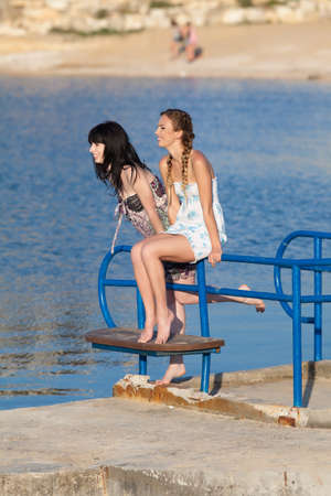 piedi nudi di bambine: Le giovani donne su sfondo d'acqua. Due ragazze a piedi nudi in prendisole sul molo Archivio Fotografico