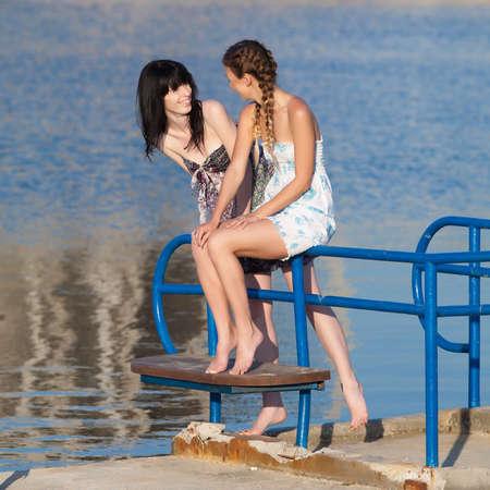piedi nudi di bambine: Le giovani donne su sfondo d'acqua. Due ragazze a piedi nudi in prendisole a parlare sul molo