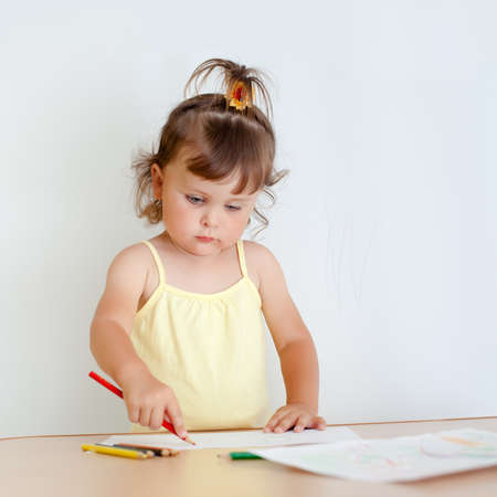 Charming toddler draws. Little girl draws photo