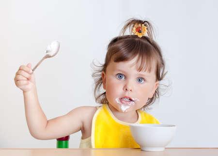 Charming toddler eats. Little girl eats photo