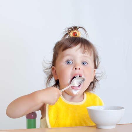 licking: Charming toddler eats. Little girl eats