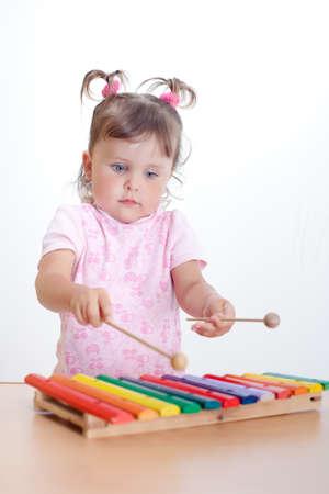 Charmant peuter speelt op xylofoon. Meisje speelt op xylofoon
