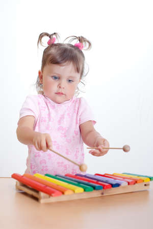 Charming toddler plays on xylophone. Little girl plays on xylophone Фото со стока