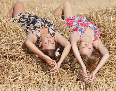 Two girls lying on hayloft photo