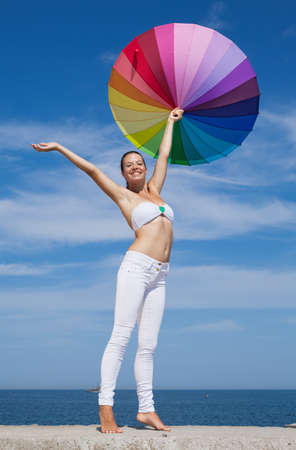 Woman carrying iridescent umbrella  Girl with iridescent umbrella on background of sky photo