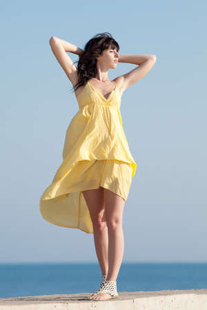 Brunette in yellow on background of sky  Young woman posing on open air photo