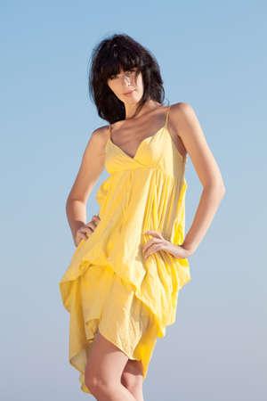 Brunette in geel op de achtergrond van hemel Jonge vrouw die zich op de open lucht