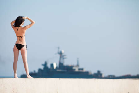 Brunette in black swimwear observing military ship  Rear view of young woman standing on open air photo