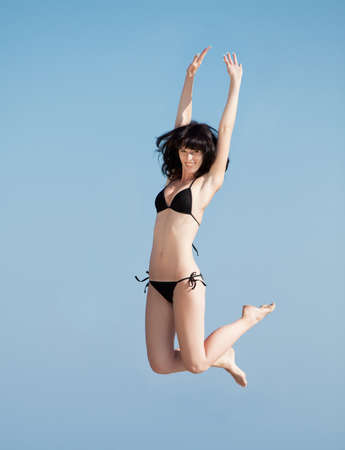 Brunette in black swimwear hopping on background of sky  Young woman jumping on open air photo