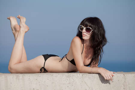 Brunette in black swimwear lying on front on open air  Young woman tans on open air photo