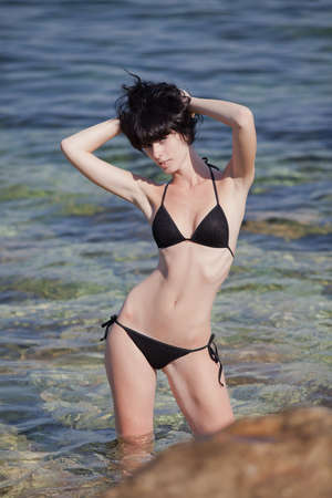 Brunette in black swimwear in the sea  Young woman posing on open air photo
