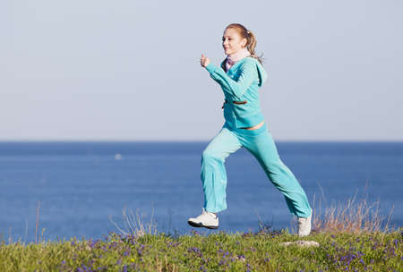 Jogging  Slim girl runs on background of sea Imagens