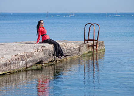 Seascape with young woman in red  Brunette in a red blouse sitting on the pier at the sea photo