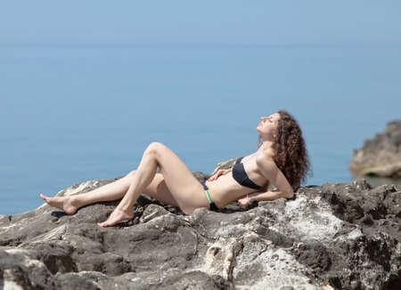 tans: Attractive young woman in black swimwear on rock  Curly girl in bikini tans