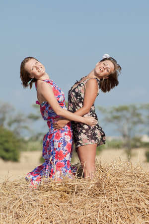 hayloft: Two girls in field  Two young woman posing on hay looking at camera smiling