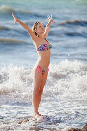 Girl at the sea  Attractive young woman with hands raised standing in line of surf photo