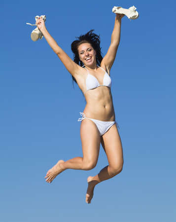 Girl at the sea  Young woman in white swimwear jumping against the sky with stiletto heels in her hands looking at camera smiling