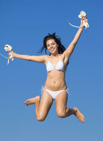 russian ethnicity: Girl at the sea  Young woman in white swimwear jumping against the sky with stiletto heels in her hands looking at camera smiling