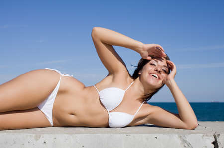 girl undressing: Girl at the sea  Young woman in white bikini lying on side looking at camera smiling
